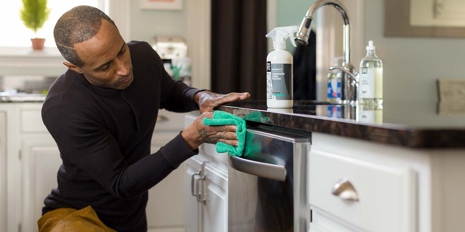 An man scrubbing the front of a dishwasher with Better Life's Stainless Steel Polish