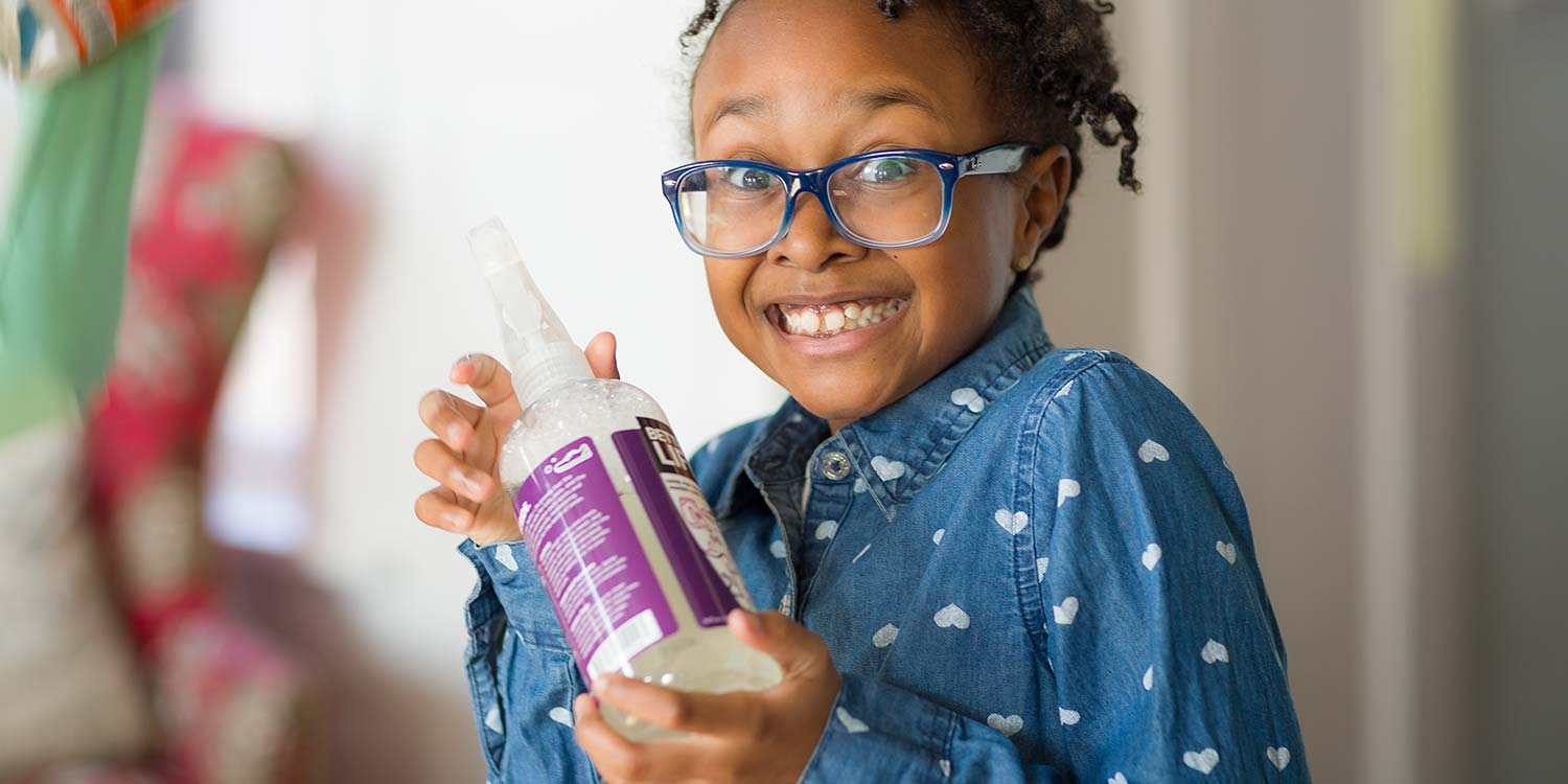 A young girl with a huge smile holding up a Better Life product in her hands