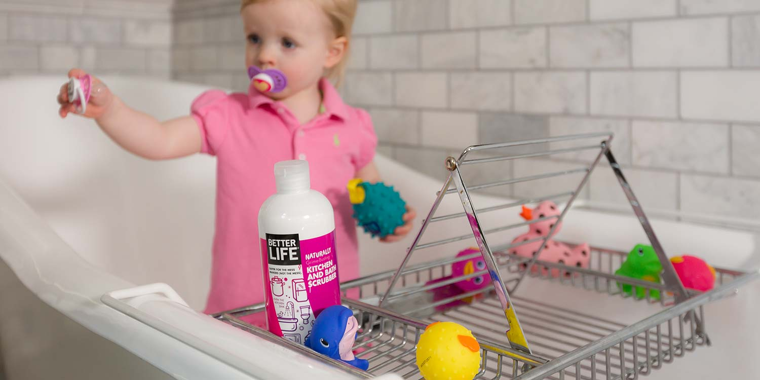 An infant in a bath tub with toys featuring Better Life's kitchen and bath scrubber