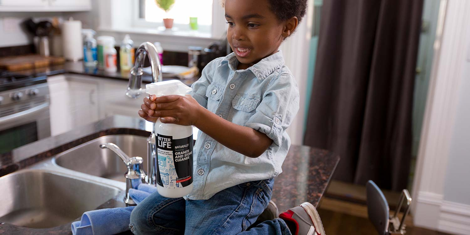 A super excited kid kneeling down on a granite countertop spraying Better Life's Stone and Granite Cleaner