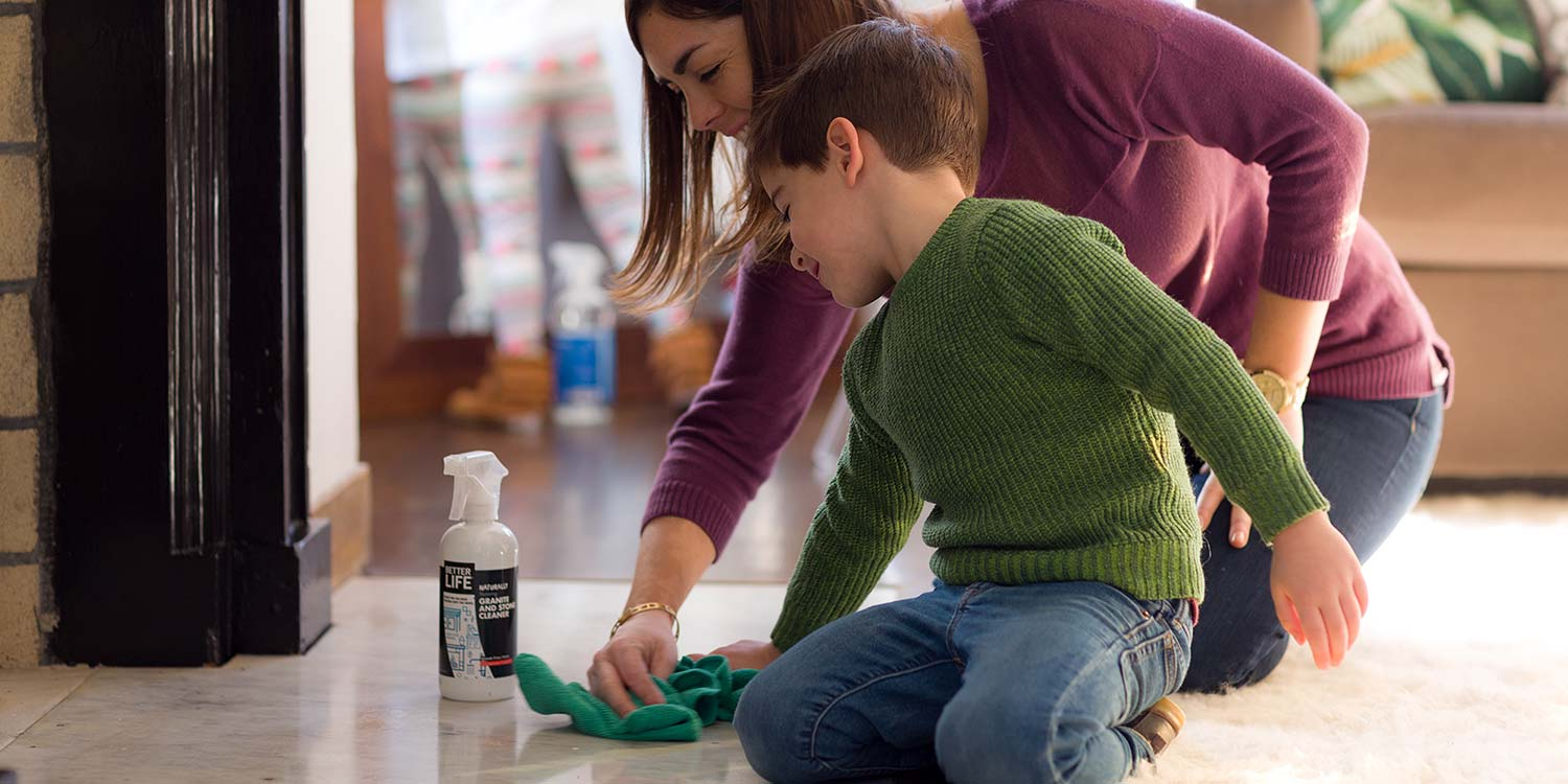 A mother and son cleaning a floor with Better Life's Graninte and Stone Cleaner