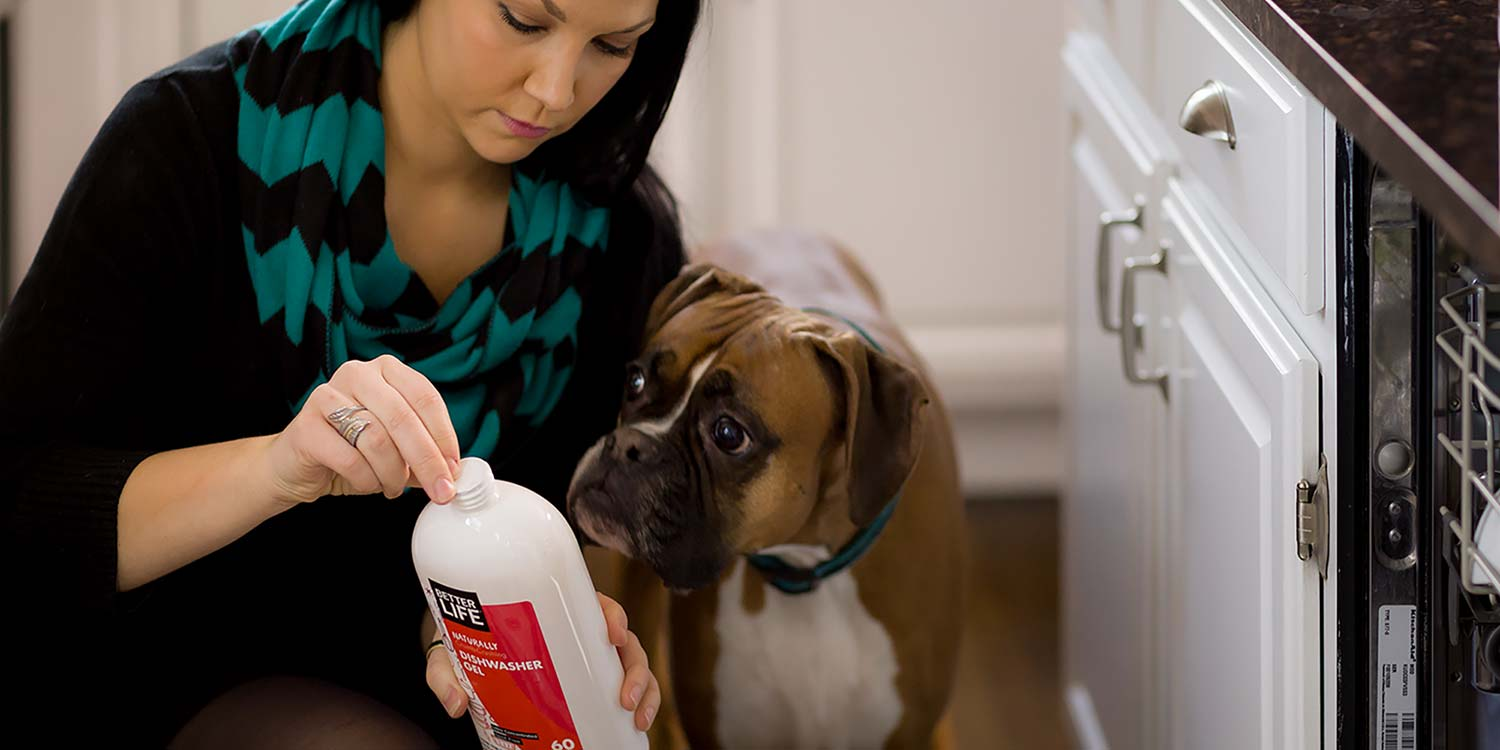 A woman opening up a bottle of Better Life's Dishwasher Cleaner with a puppy dog watching closely