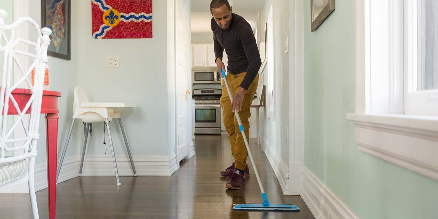 A man cleaning a hardwood floor with a blue sweeper