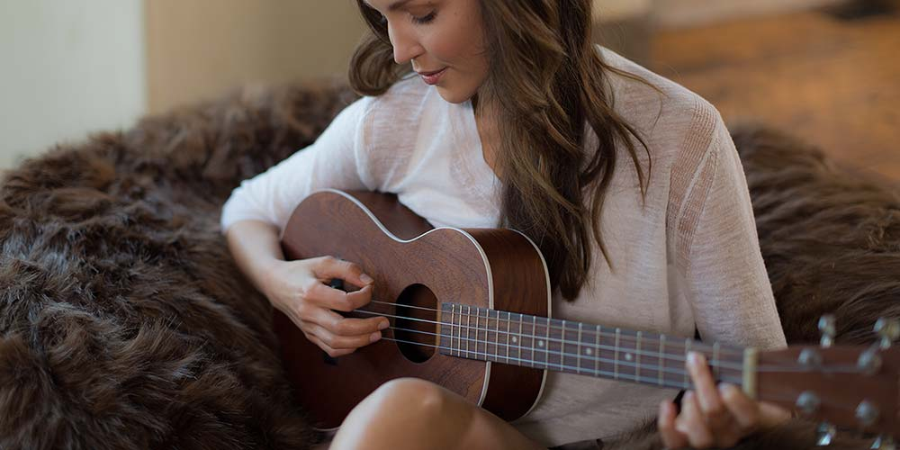 An image of a woman sitting comfortably on a furry Comfy Sack while strumming a guitar