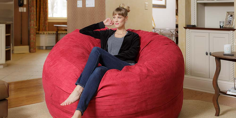 An image of a woman dressing comfortably while sitting on a Comfy Sack