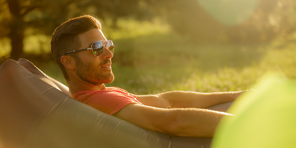 An image of a man relaxing on a Comfy Sack's Nomad Lounger during the setting of the sun