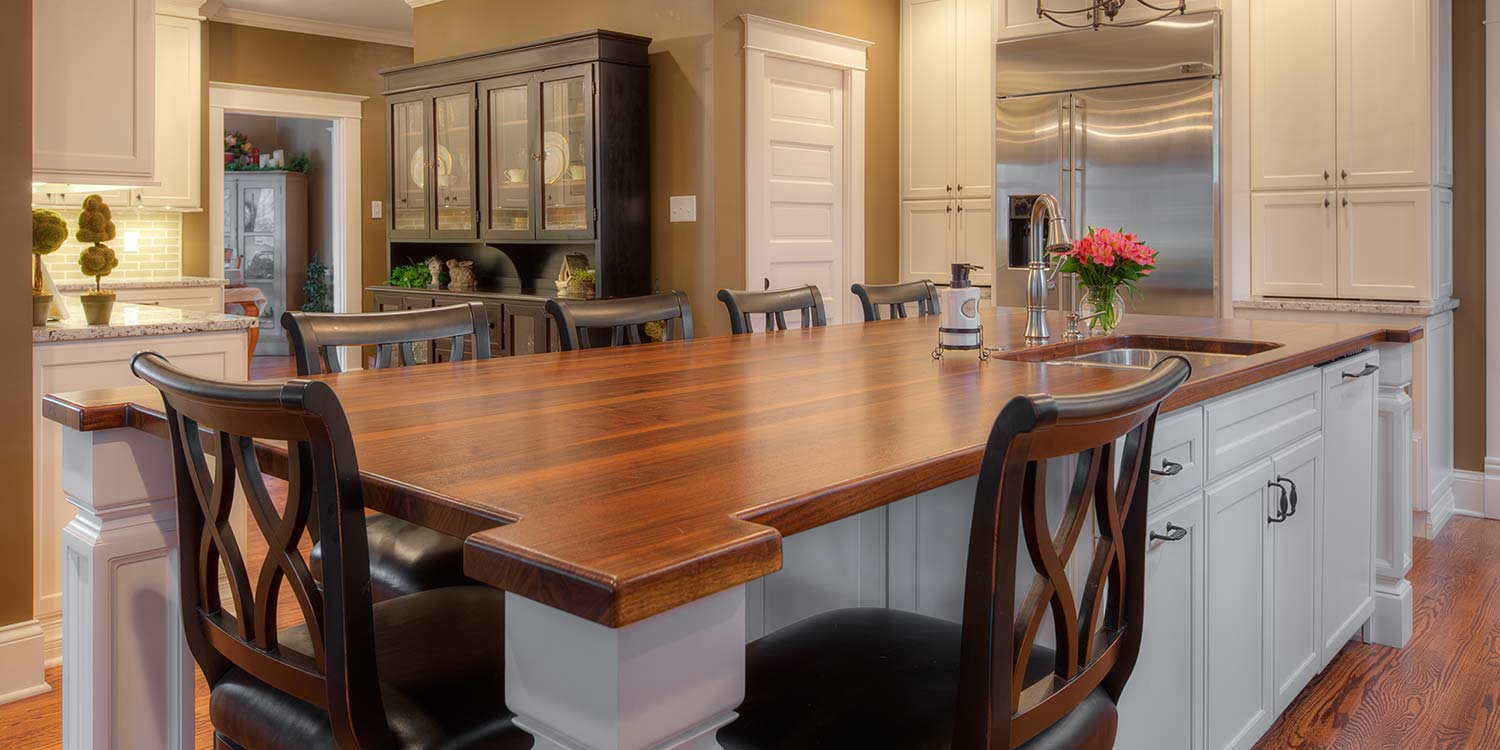 An image of a beautiful wood countertop placed inside of a complete kitchen