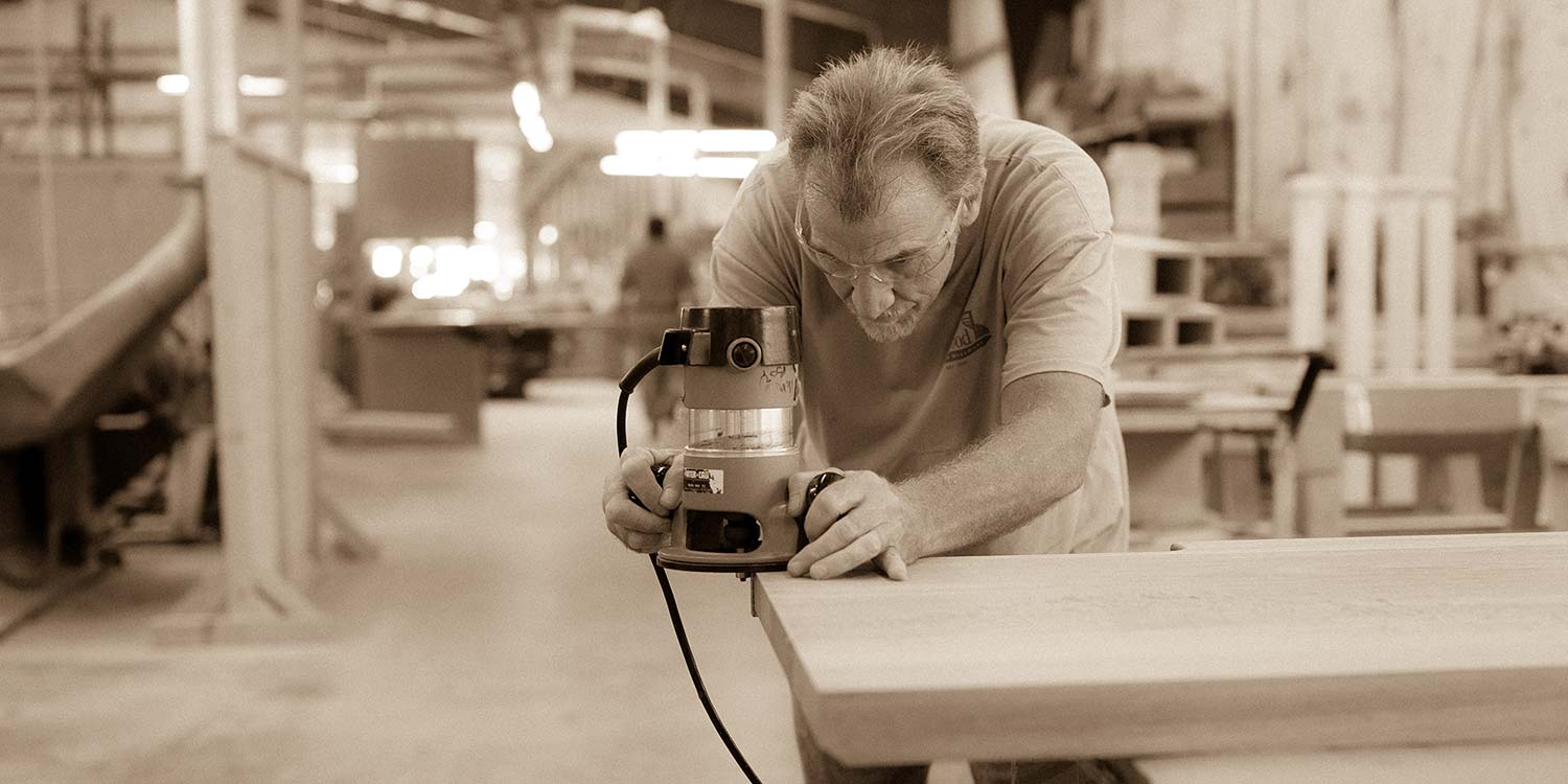 An image of a Kstair worker trimming up the edges of a piece of lumber