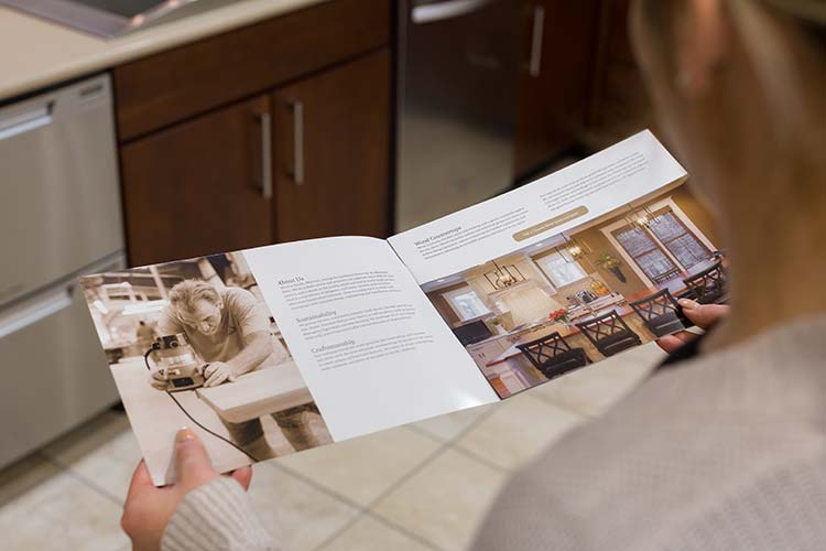 A person looking through a Kirkwood Stair pamphlet showing a person working, some text, and a completed kitchen