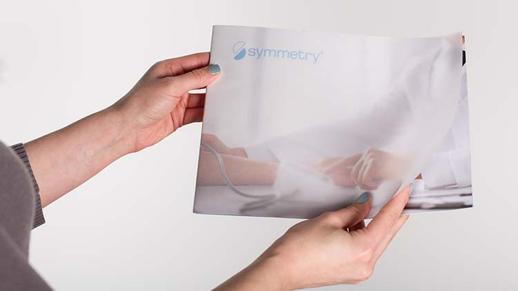 The front cover of a Symmetry pamphlet showing a doctor's hands