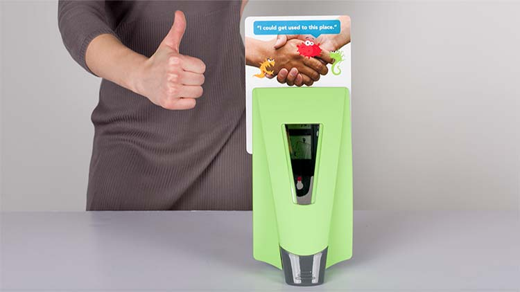A person giving a thumbs up after successfully placing a placard behind a green symmetry dispenser